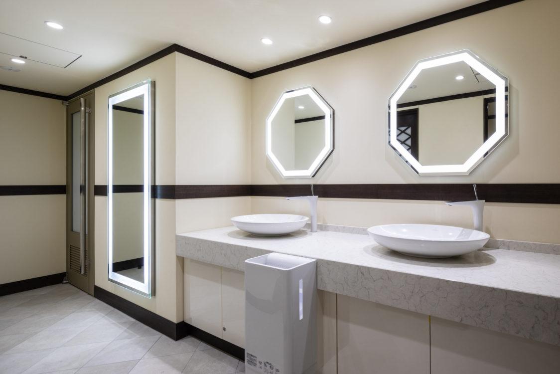 地下階のトイレも建設当時予想ができなかった女性利用者増加にも対応した配慮をはじめ、明るく美しいトイレを目指した。またLED照明に更新した大道場でのイベントでの登壇者などに配慮して各所で可能な限り近い状態で身なりを整えることができるよう照明付きの鏡をデザインするなど細部にも配慮した。 The toilet on the basement floor was also designed to be bright and beautiful, including consideration for the increase in female users, which was unpredictable at the time of construction. In addition, consideration was given to details such as designing illuminated mirrors so that the appearance could be adjusted as close as possible to each place in consideration of the speakers at the event at the main dojo, which was updated with LED lighting.