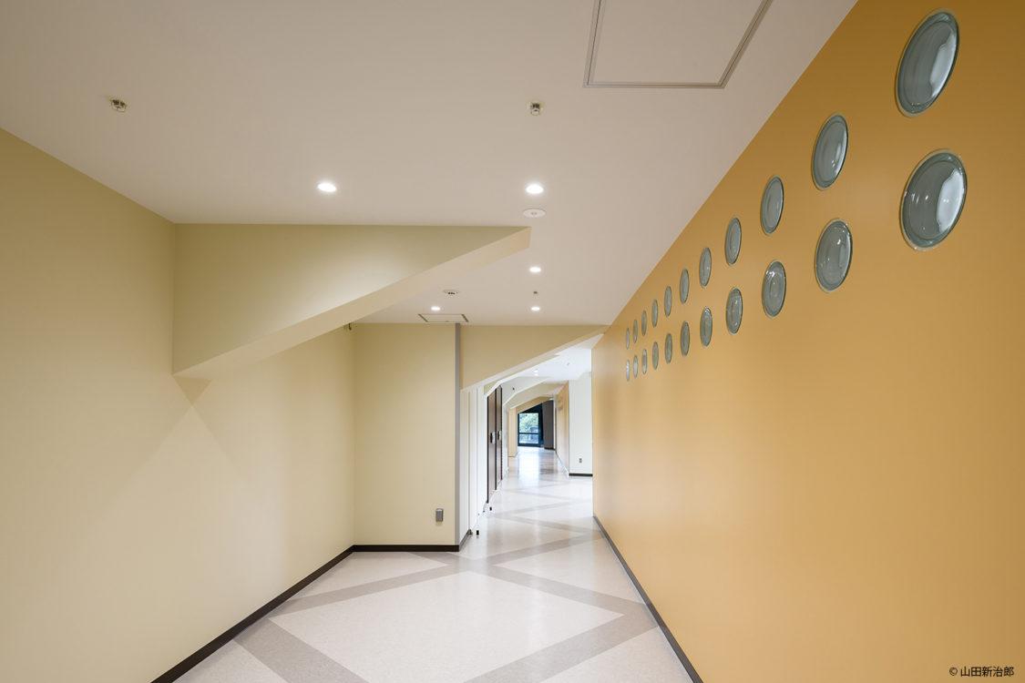 2階ロビーには、山田守がよく設計で多用していた丸ガラスブロックを新たにアクセントとして設置した。2階の廊下に公園の光を取り入れるためでもある。アクセントとして一部壁の色を変えてリズムを生み出した。撮影:山田新治郎 In the 2nd floor lobby, round glass blocks, which Mamoru Yamada often used in his design, were newly installed as an accent. It is also to let in the light of the park in the 2nd floor corridor. As an accent, we changed the color of a part of walls to create a rhythm.
