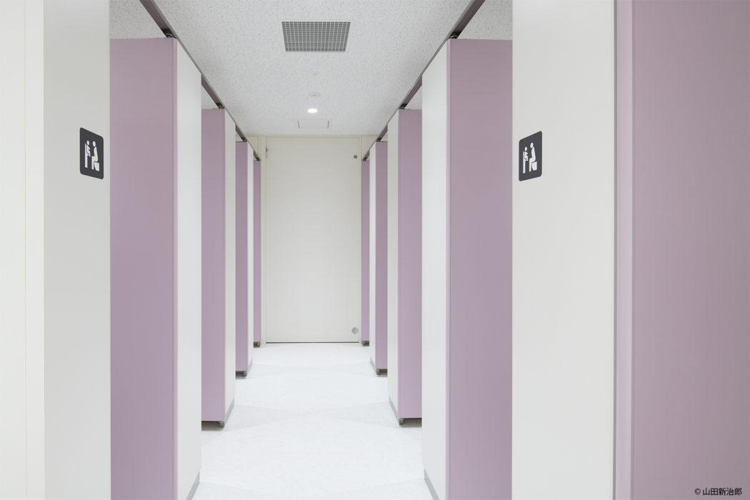 【男女の比率が変更可能なトイレ1】2枚の間仕切り壁の開閉により比率を変更が可能となり本館のトイレの数も補完できるように配慮している。   撮影:山田新治郎