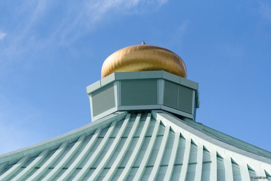 山田守は、金の擬宝珠は、武道の心のシンボルと語る。引き続き避雷針としての役割も担っている。既存の外観を大きく変えないため、擬宝珠下の換気ガラリを一部排煙窓に改修し、大道場に自然排煙を確保し安全性の向上を行った。 撮影:山田新治郎 Mamoru Yamada says that the gold giboshi is a symbol of the budō spirit. It continues to play a role as a lightning rod.